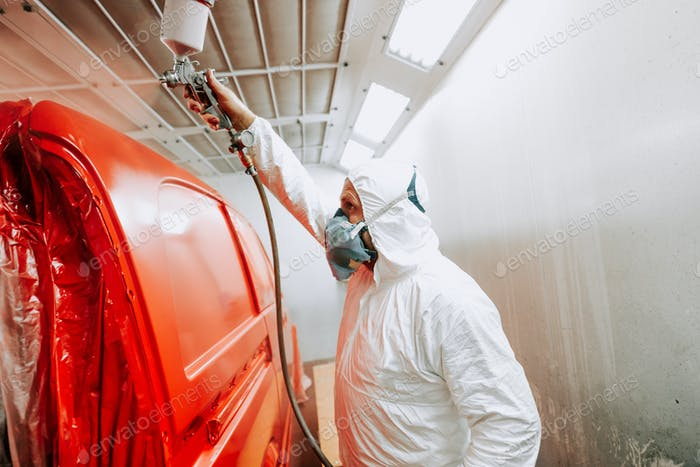 Worker painting a red multivan or car in auto garage using an airbrush gun