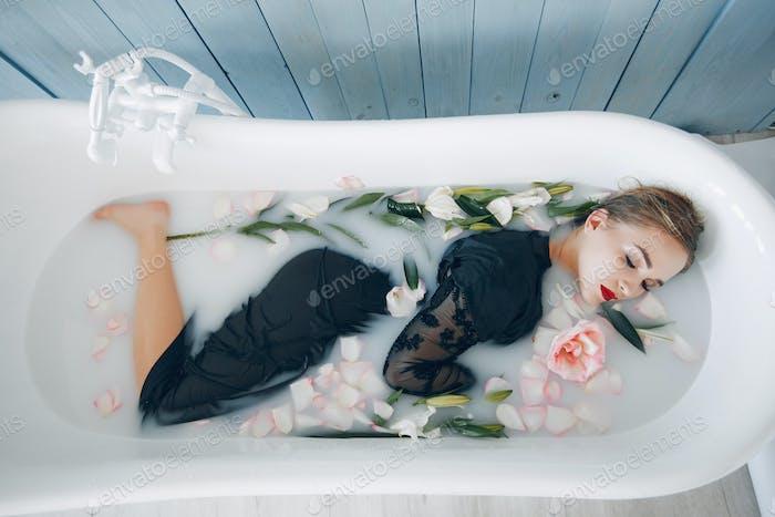 Stylish and beautiful girl lies in the bathroom