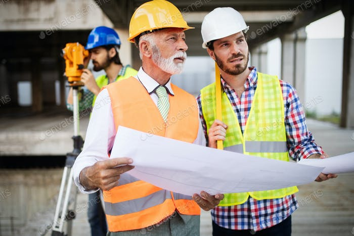 Construction engineers discussion with architects at construction or building site