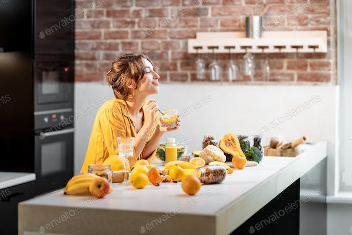 Woman eating healthy fresh food in the kitchen