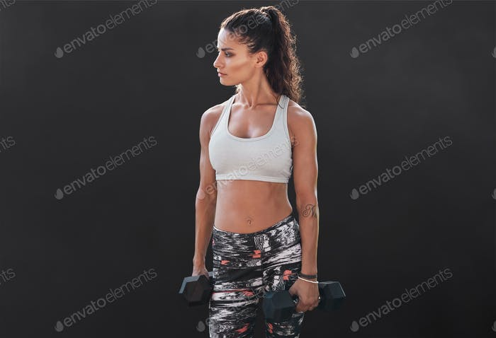 Slim and fit woman lifting hand weights