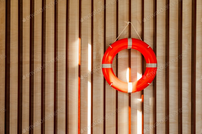 Red lifebuoy hanging on blue wooden wall of a port building