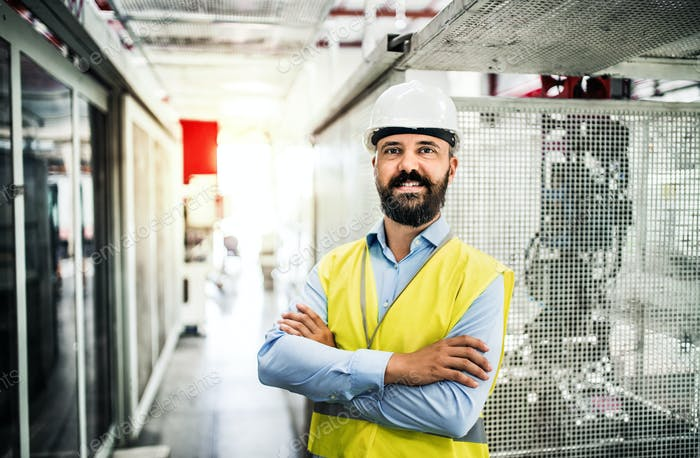 A portrait of an industrial man engineer in a factory, arms crossed.