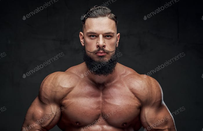 Powerful guy with naked torso posing in dark background
