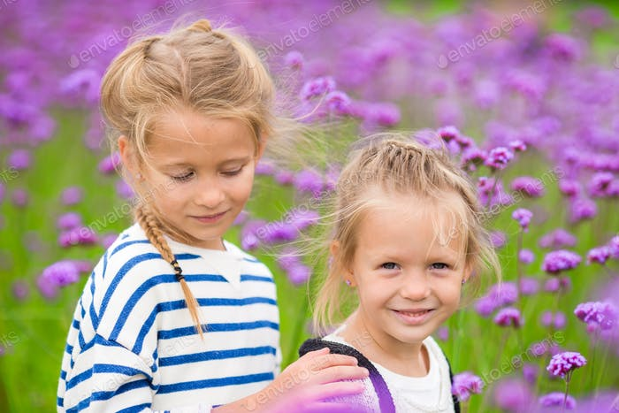 Little adorable girls walking outdoors in flowers field