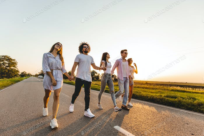 Company of happy young stylish guys hold their hands and walk on a country road on a sunny day