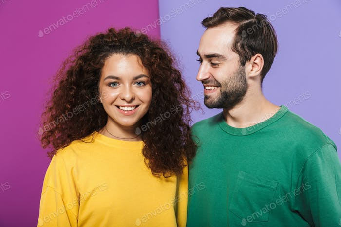 Portrait of brunette caucasian couple in colorful clothing smiling together, man looking at woman