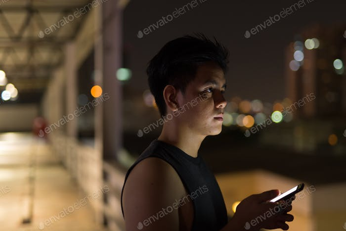 Young handsome Asian man thinking while using phone against view of the city at night