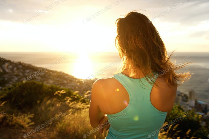 Sporty woman from behind watching the sunset