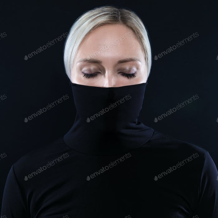 Studio portrait of beautiful elegant woman hiding face in black turtleneck