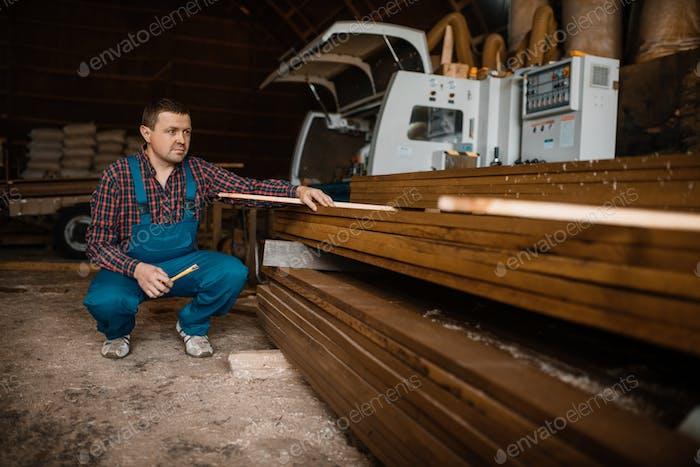 Tischler in Uniform an seinem Arbeitsplatz auf Sägewerk
