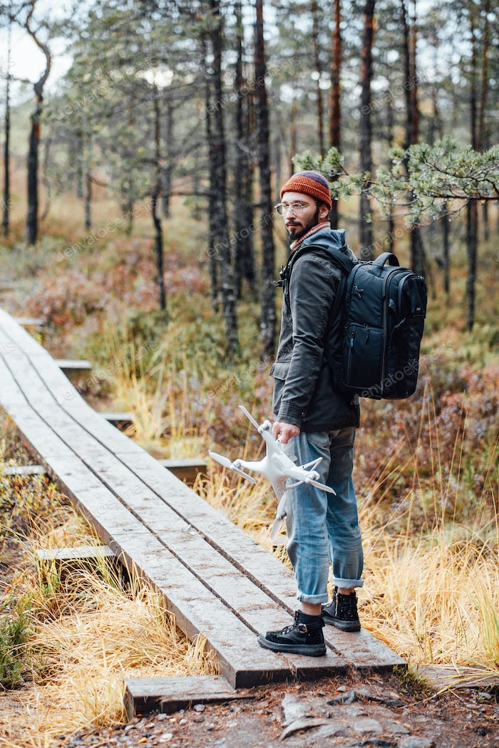 Bearded guy staying and looking at camera in wooden road
