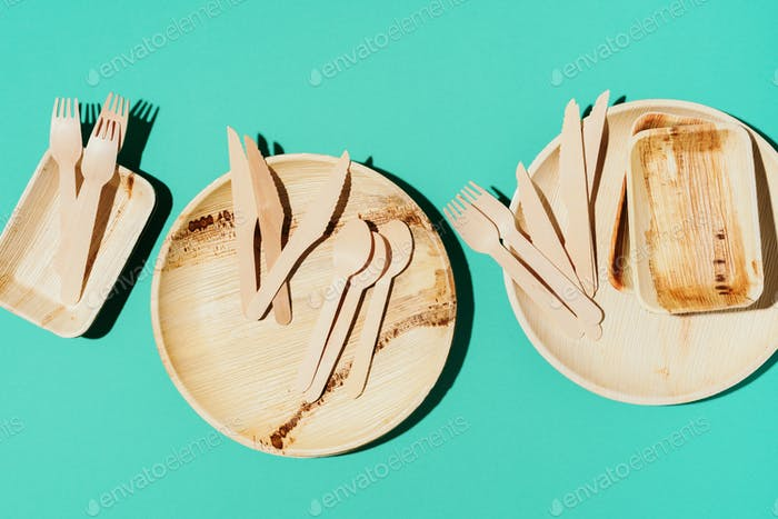 Eco craft paper tableware. Paper cups, bamboo wood dishes and wooden cutlery on blue background