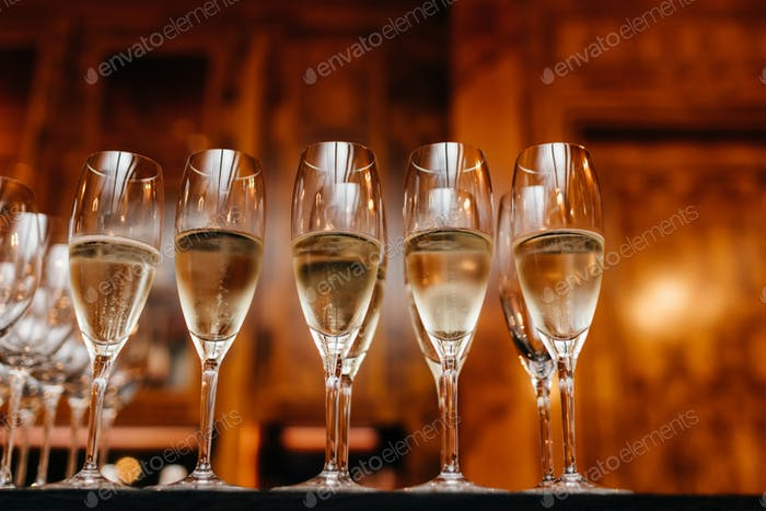 Horizontal shot of glasses with white wine or champagne in row against blurred background