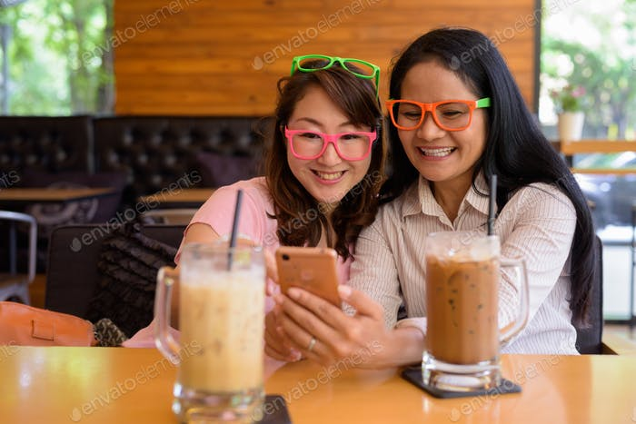 Two mature Asian women together hanging out at the coffee shop