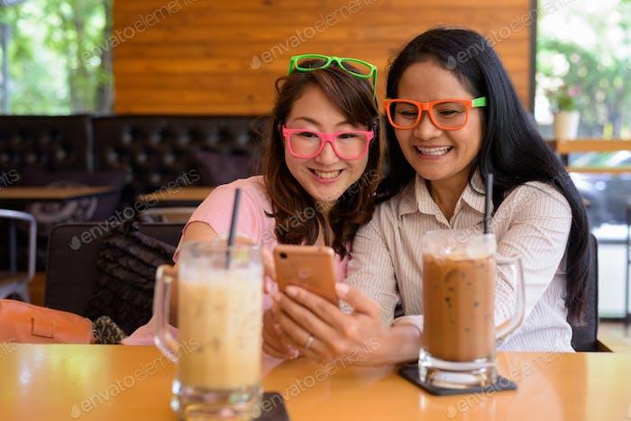 dos maduro asiático las mujeres juntos pasando fuera en el café tienda