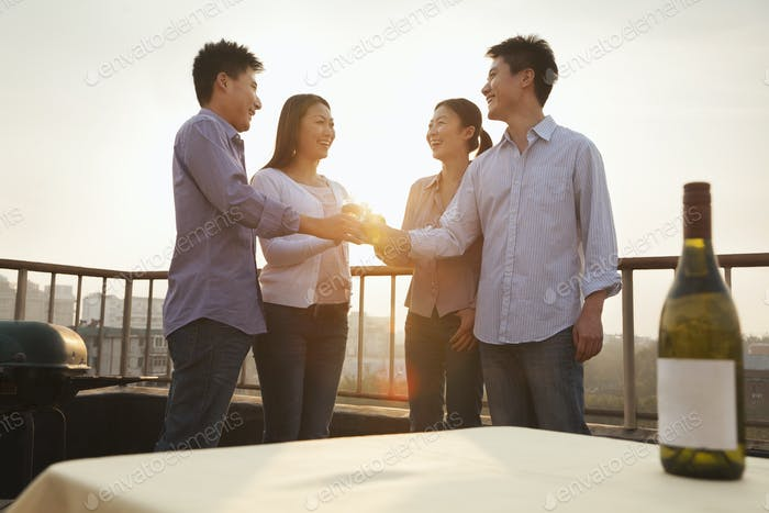 Group of Friends Toasting Each Other on Rooftop at Sunset