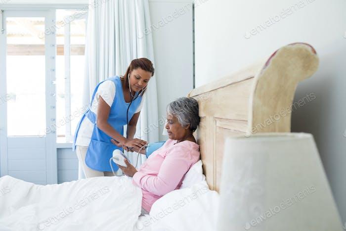 Female doctor measuring blood pressure of senior woman in bedroom
