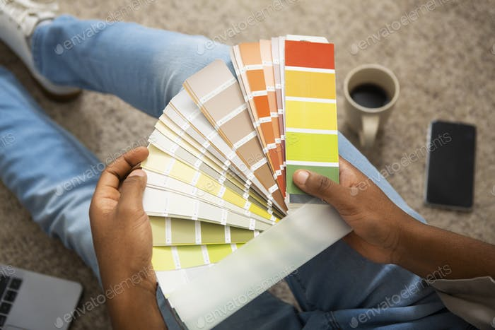 African american man millennial holds color swatch