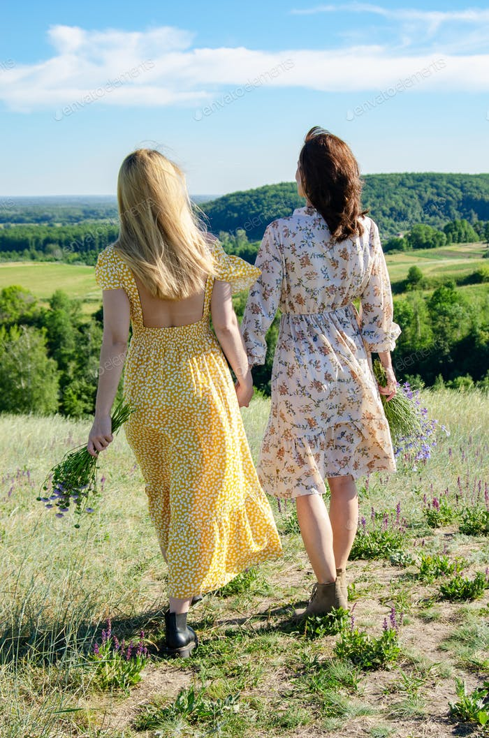 Two caucasian female models walk outdoors holding their hands
