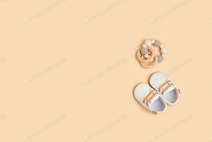 Gender neutral baby shoes and accessories over beige background