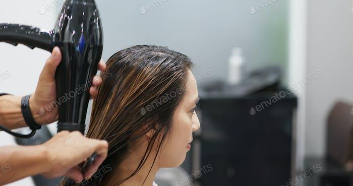 Hair dresser drying woman hair in salon