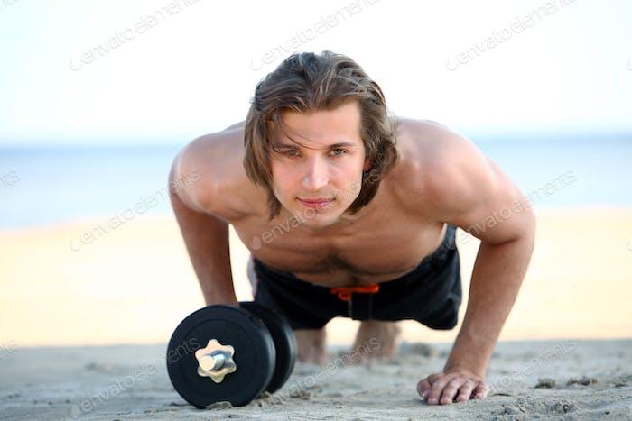 Красивый мужчина делает фитнес-упражнения на пляже