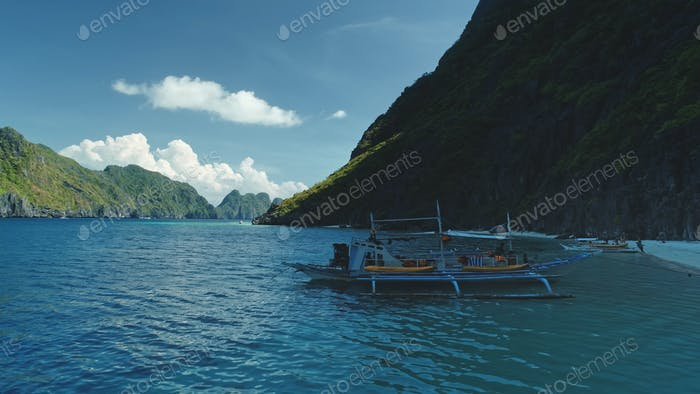 Closeup passenger boats at ocean coast with cliff shore at summer tour. Serene tropical nature scape
