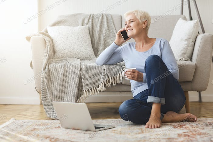 Joyful elderly business lady talking with clients from home
