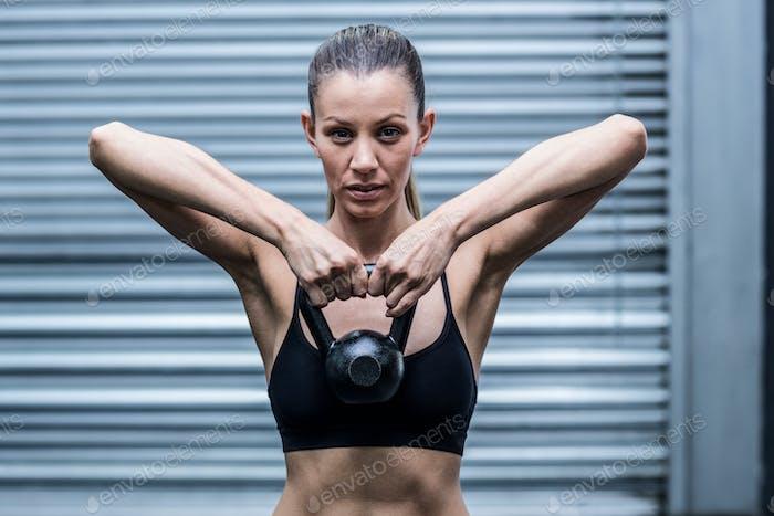 Porträt einer muskulösen Frau heben Kettlebells
