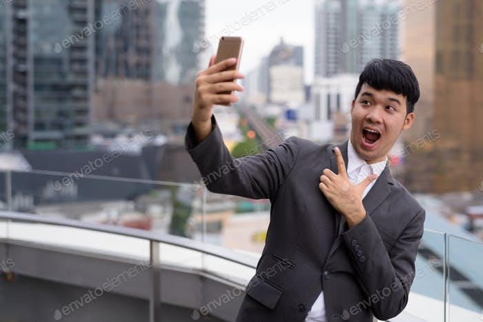 Portrait of young Asian businessman using phone against view of the city