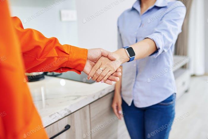 Reparaturmann schüttelt die Hand der Hausfrau