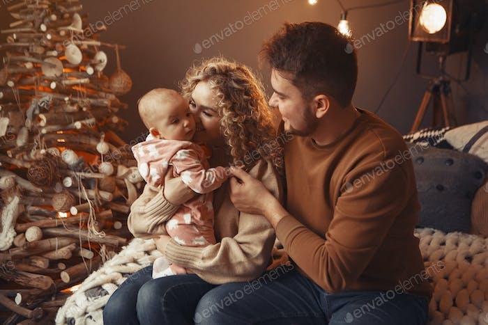 Elegante Familie sitzt zu Hause in der Nähe von Weihnachtsbaum