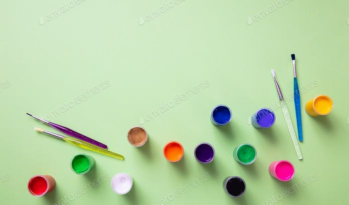 Colorful finger paints set on green color background, top view