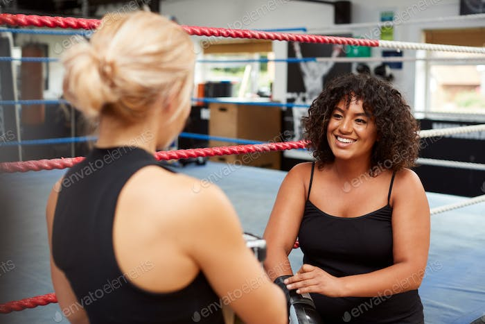 Personal Trainer Helping Female Boxer In Gym To Put On Boxing Gloves In Gym