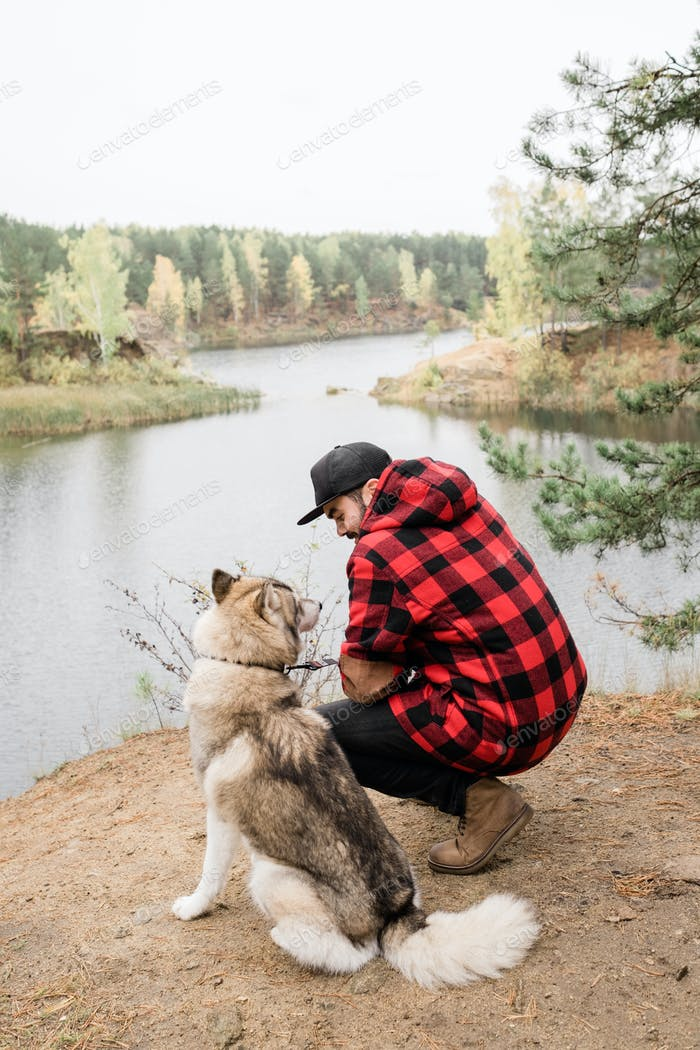 Young man in checkered jacket and black jeans sitting on squats by purebred pet