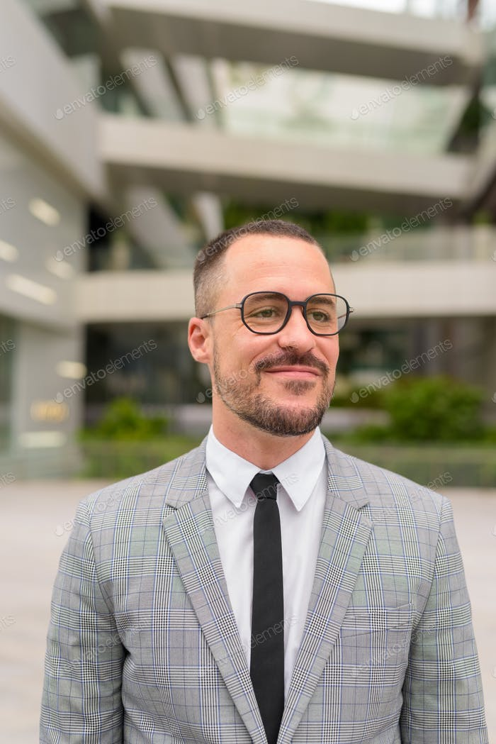 Face of Hispanic bald bearded businessman with eyeglasses thinking in the city outdoors
