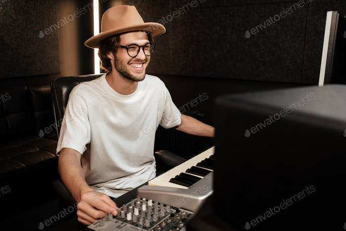 Young stylish cheerful musician happily working on new album in modern recording studio