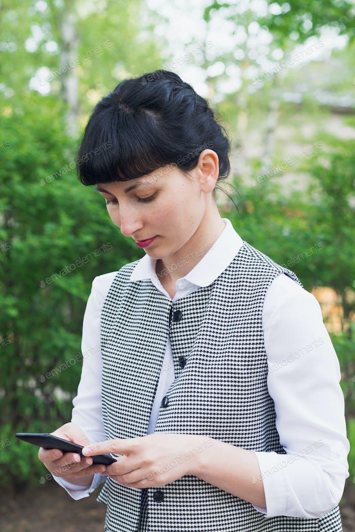 brunette caucasian businesswoman touch smartphone walking in park