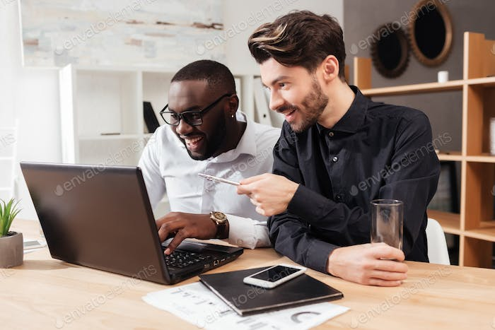 Smiling multinational businessmen sitting at the table happily working with laptop in office
