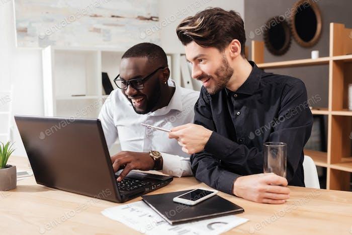 Lächelnd multinationale Geschäftsleute sitzen am Tisch glücklich arbeiten mit Laptop im Büro