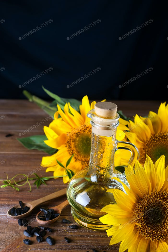 Organic sunflower oil in a small glass jar with sunflower seeds and fresh flowers.