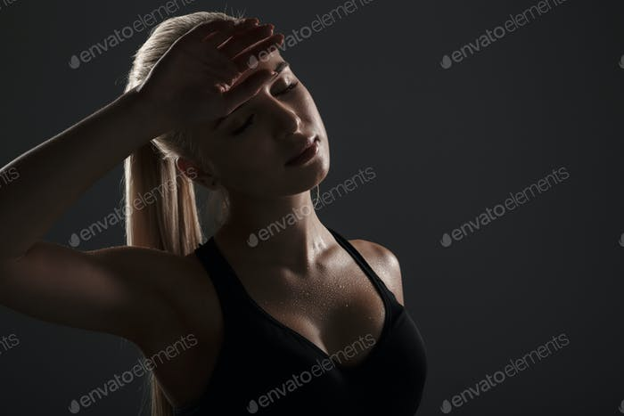 Side view of a tired fitness woman dressed in sportswear