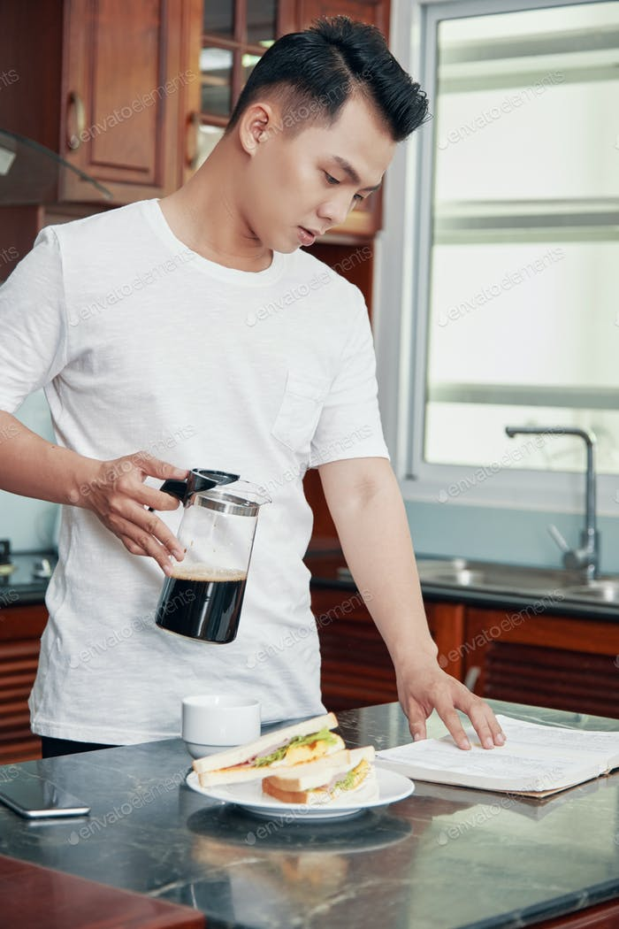 Young Asian man reading papers during breakfast