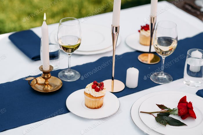 Table setting, glasses, candles, flower and sweets