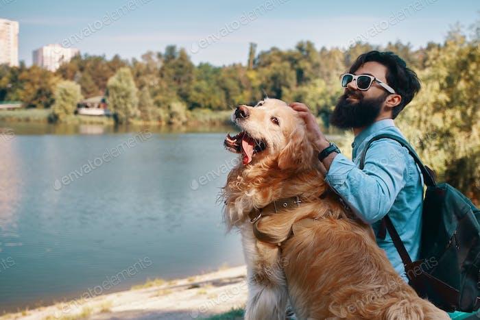 Молодой человек сидит с собакой на стуле в парке, наслаждайтесь