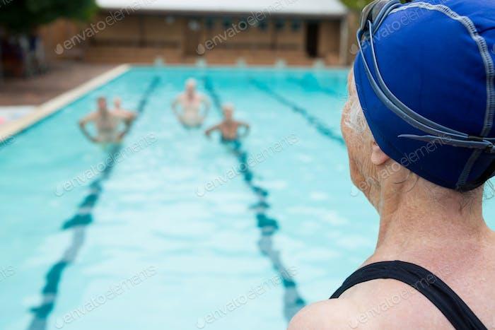 Senior woman looking at swimming pool