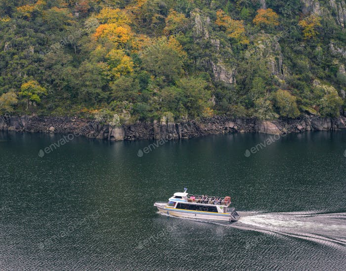 Tourists on a boat enjoy the views of the Sil River Canyon
