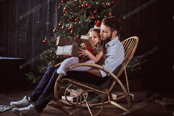 Dad and daughter holding gift boxes while sitting together on a rocking chair