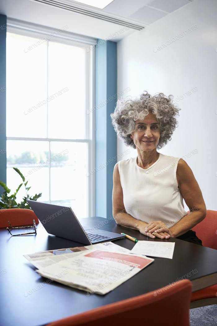 Middle aged woman in an office smiling to camera, vertical